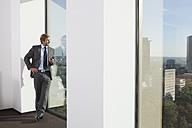 Germany, Frankfurt, Businessman using phone in office - SKF000468
