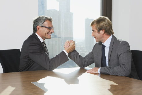 Germany, Frankfurt, Businessmen doing arm wrestling - SKF000513