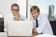 Germany, Frankfurt, Businessmen using laptop in office - SKF000516