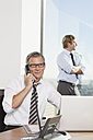 Germany, Frankfurt, Businessman on the phone with man in background - SKF000519