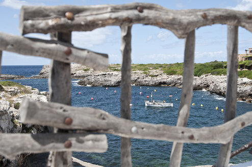 Spain, Balears, Menorca, View of boat in sea from wooden fence - UMF000306