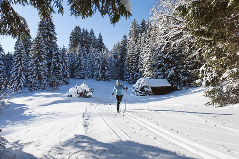 Germany, Bavaria, Isar Valley, Senior woman doing cross country skiing - MIRF000092