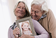 Germany, Wakendorf, Grandparents holding granddaughter photograph - WESTF016230