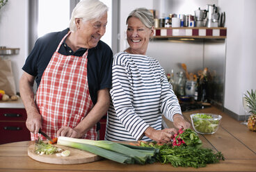Germany, Wakendorf, Senior couple cutting vegetables in the kitchen - WESTF016248
