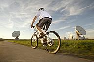 Germany, Bavaria, Raisting, Man riding electric bicycle near radio station - RNF000662