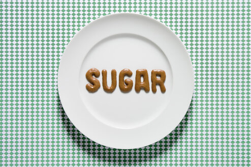 Word sugar written with russian bread on dish, close up - MUF000989