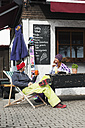 Austria, Kleinwalsertal, Couple relaxing outside mountain hut, man drinking juice - MRF001248