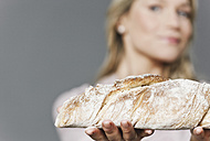 Mid adult woman holding bread - WESTF016266