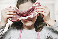 Germany, Cologne, Girl holding a slice of meat - WESTF016293