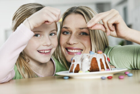 Germany, Cologne, Mother and daughter decorating cake, smiling, portrait - WESTF016326