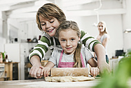 Germany, Cologne, Boy and girl rolling dough, mother in background - WESTF016362