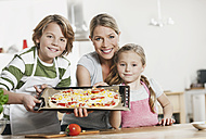 Germany, Cologne, Mother and children making pizza in kitchen - WESTF016365