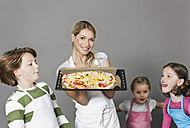 Mother and children with pizza in baking tray - WESTF016368