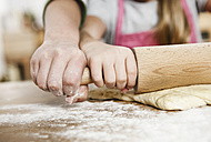 Germany, Cologne, Boy and girl rolling dough on kitchen worktop - WESTF016377