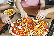 Germany, Cologne, Mother and children garnishing pizza - WESTF016380
