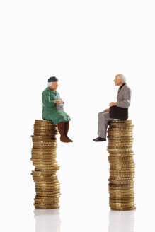 Figurines grandma and grandpa sitting on coin stack - CSF014720