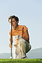 Italy, Kastelruth, Mid adult woman holding golf club on golf course - WESTF016480