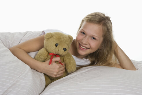Girl lying on bed with teddy bear, smiling - WWF001873