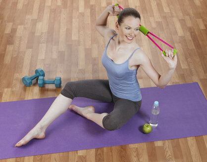 Young woman doing exercise, smiling, portrait - JLF000335