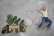 Young man lying by fruits and vegetables connected with electric cable - BAEF000206