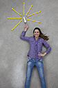 Mid adult woman pointing at electric bulb, smiling, portrait - BAEF000215