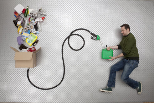 Mid adult man holding petrol can and hose connected to cardboard box - BAEF000230