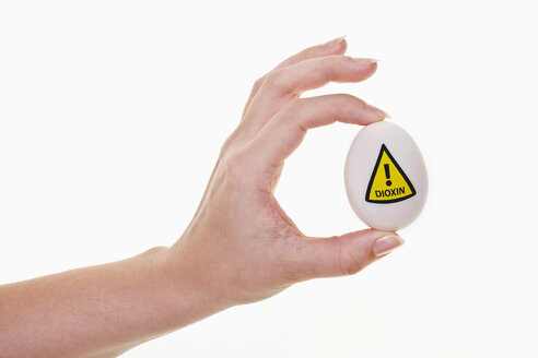 Human hand holding egg with warn sign of dioxin - TSF000189