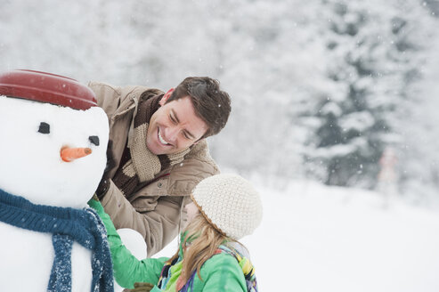 Austria, Salzburg, Hüttau, Father and daughter with snowman, smiling - HHF003612