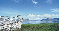 Iceland, Snaefelnes, View of old boat at fjord shore with mountains - WBF000853