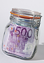 Close up of euro notes in airtight glass jar against white background - WBF001008