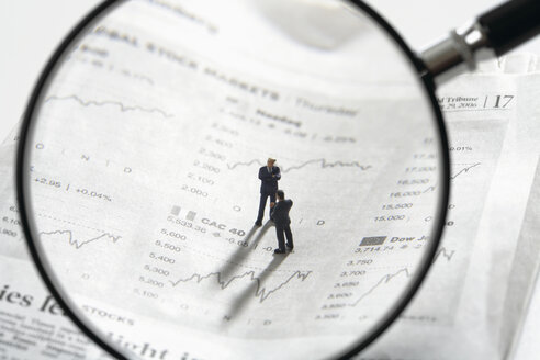 Two figurines on newspaper stock quotes with magnifying lens in foreground - WBF001010