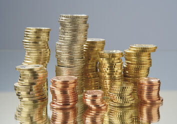 Close up of variety of euro coins stacked against grey background - WBF001018