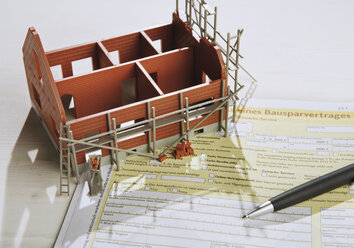 Model house on building loan form, close up - WBF001038