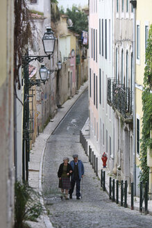 Portugal, Lisbon, Elderly couple walking along cobbled street in bairro alto district - PS000470