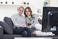 Germany, Munich, Young friends watching tv, smiling - RBF000532