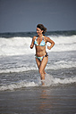 Greece, Crete, Mature woman running in water - AKF000336