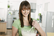 Germany, Cologne, Woman mixing batter in bowl - FMKF000182