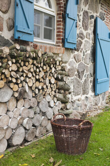 Germany, Kratzeburg, Basket and stack of firewoods near country house - WESTF016577