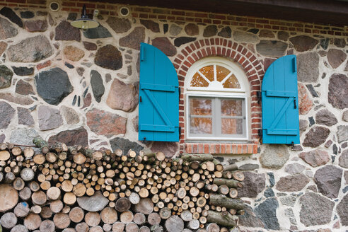 Germany, Kratzeburg, Stack of firewood near country house - WESTF016583