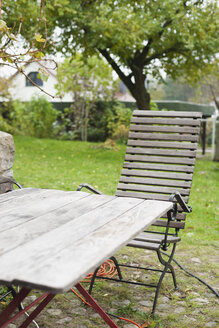 Germany, Kratzeburg, Empty chair and table at garden near country house - WESTF016586