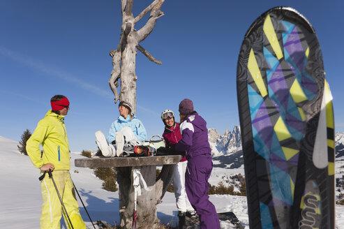 Italy, Trentino-Alto Adige, Alto Adige, Bolzano, Seiser Alm, People with skiing equipments resting near bare tree on snowy landscape - MIRF000119