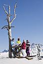 Italy, Trentino-Alto Adige, Alto Adige, Bolzano, Seiser Alm, People resting near bare tree on snowy landscape - MIRF000122