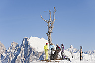 Italy, Trentino-Alto Adige, Alto Adige, Bolzano, Seiser Alm, People resting near bare tree on snowy landscape - MIRF000125