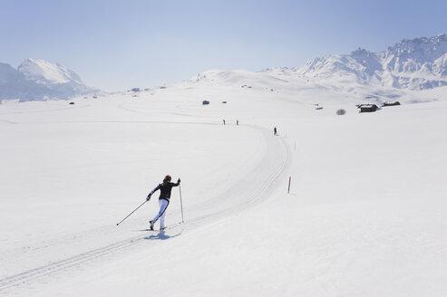 Italy, Trentino-Alto Adige, Alto Adige, Bolzano, Seiser Alm, Mid adult woman doing cross-country skiing - MIRF000161