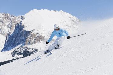 Italy, Trentino-Alto Adige, Alto Adige, Bolzano, Seiser Alm, Young woman skiing near mountain - MIRF000173