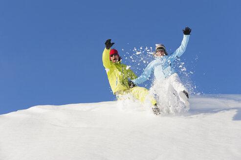 Italy, Trentino-Alto Adige, Alto Adige, Bolzano, Seiser Alm, Man and woman jumping on snow - MIRF000185