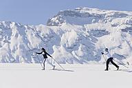 Italy, Trentino-Alto Adige, Alto Adige, Bolzano, Seiser Alm, Two women doing cross-country skiing near mountain - MIRF000194