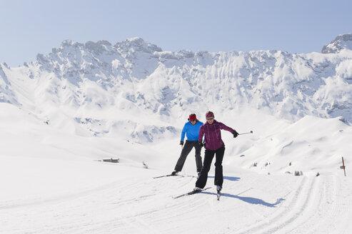 Italy, Trentino-Alto Adige, Alto Adige, Bolzano, Seiser Alm, Man and woman doing cross-country skiing - MIRF000197