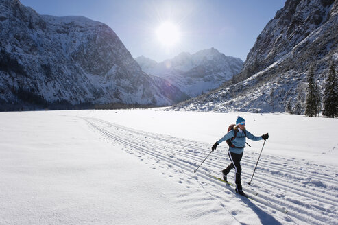 Germany, Bavaria, Senior woman doing cross-country skiing with karwendal mountains in background - MIRF000209