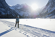 Germany, Bavaria, Senior woman doing cross-country skiing with karwendal mountains in background - MIRF000212